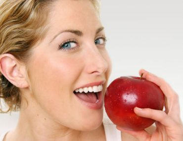 happy-woman-eating-red-apple-1